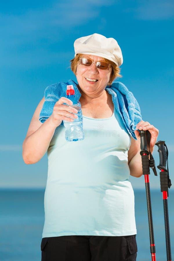 Senior woman practicing nordic walking on beach stock photo