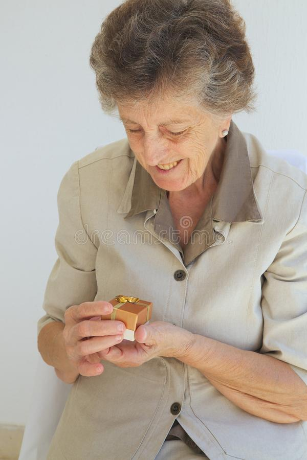 A senior woman with a present. A senior woman between 70 and 80 years old is happy to get a small present box royalty free stock images