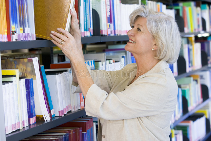 Senior woman pulling a library book off shelf.  stock photos