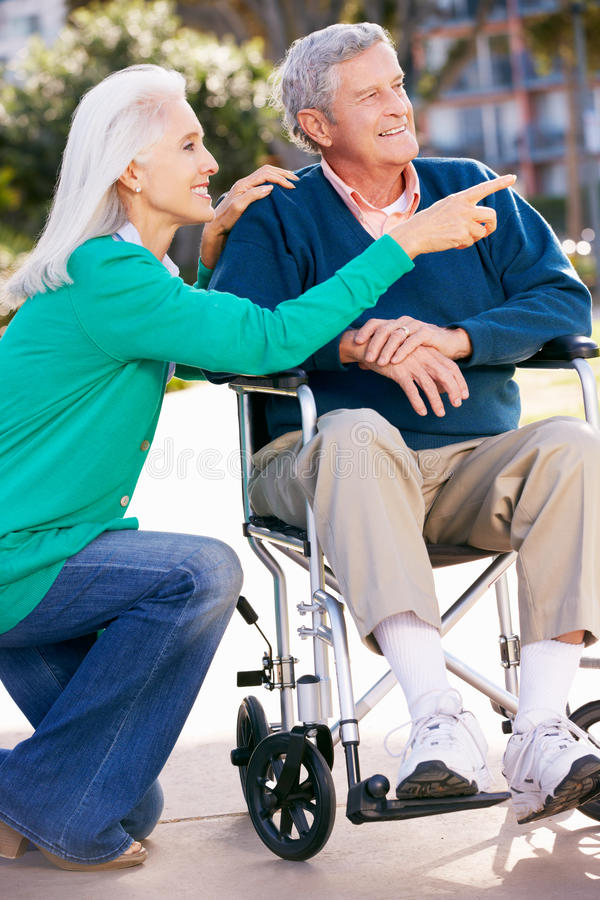Senior Woman Pushing Husband In Wheelchair Stock Photo