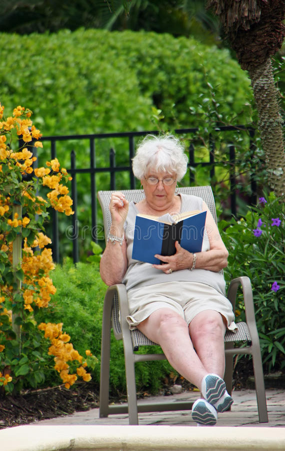 Senior woman reading book. Senior woman sat in lounge chair reading book with flowers in background stock photos
