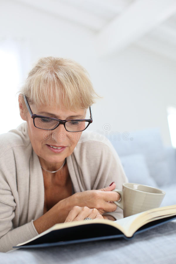 Senior woman reading book and drinking tea royalty free stock photos