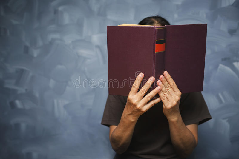 Senior woman reading a book at living room with old vintage table and concrete wall background. stock images