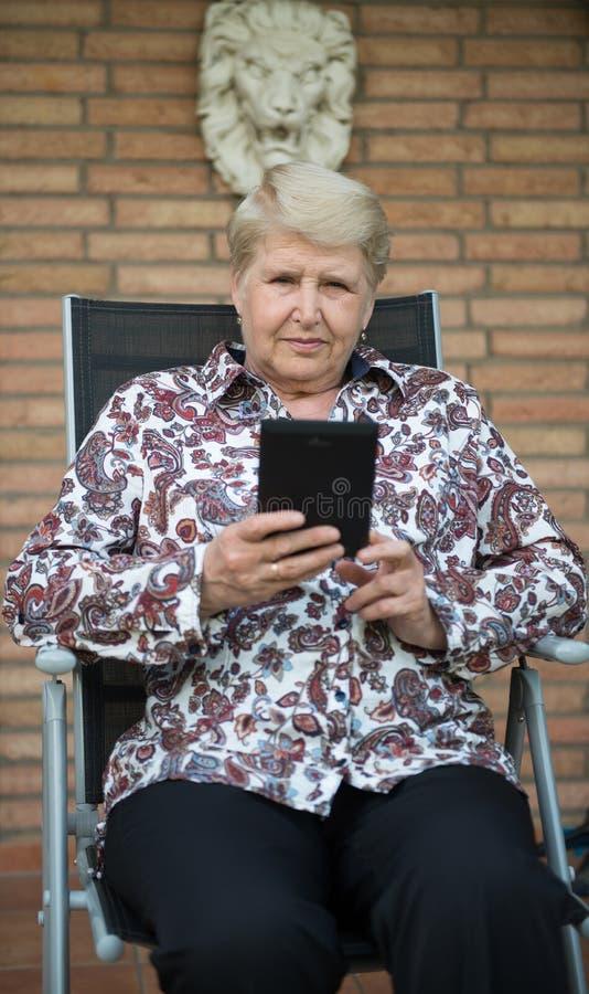 Senior woman reading e-book stock photos
