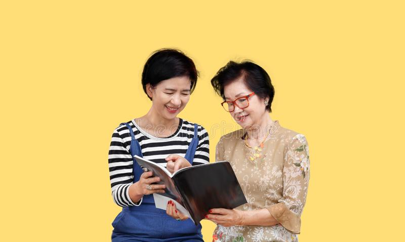Senior woman reading a magazine with her daughter royalty free stock image
