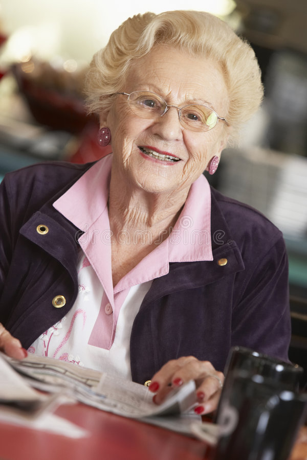 Senior woman reading newspaper royalty free stock images
