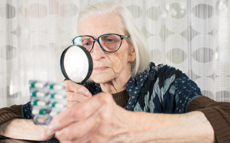 Senior woman reading pill name with magnifying glass. At home stock photo