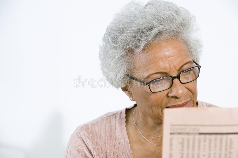 Senior Woman Reading Stocks And Shares In Newspaper. Tensed senior African American women reading stocks and shares in newspaper royalty free stock photography