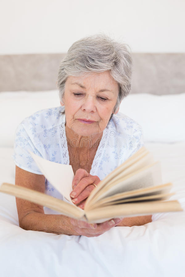 Senior woman reading story book in bed. Concentrated senior woman reading story book in bed stock photo