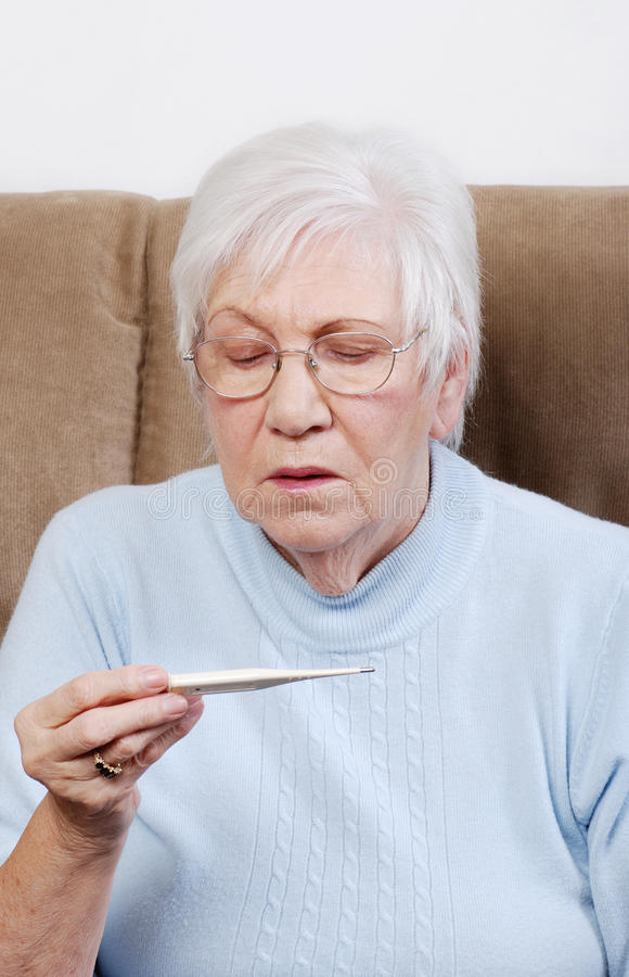 Senior woman reading a thermometer royalty free stock image