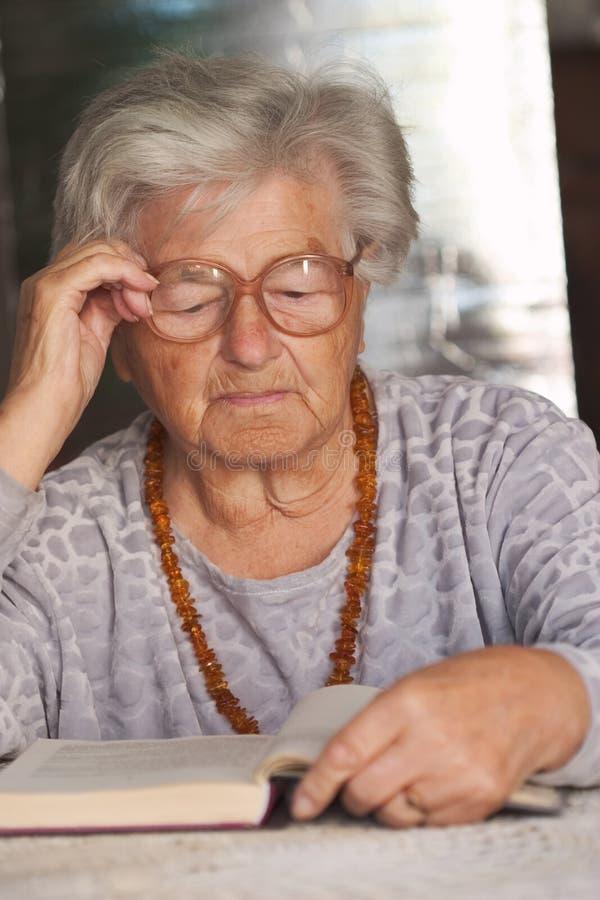 Senior woman reads a book. Elderly woman reading a book stock photography