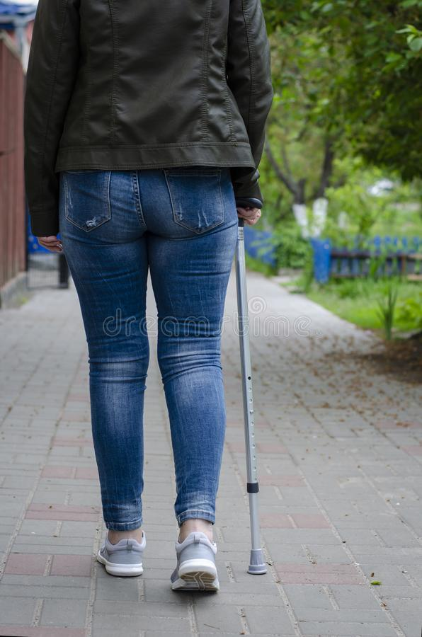Senior woman on a rehabilitation after surgery or on recovery walks with walking cane. Outdoors. Rehabilitation and healthcare concept. Vertical royalty free stock photos