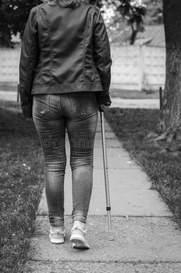 Senior woman on a rehabilitation after surgery walks with walking cane. Outdoors. Rehabilitation and healthcare concept. Black and white. Vertical royalty free stock photography