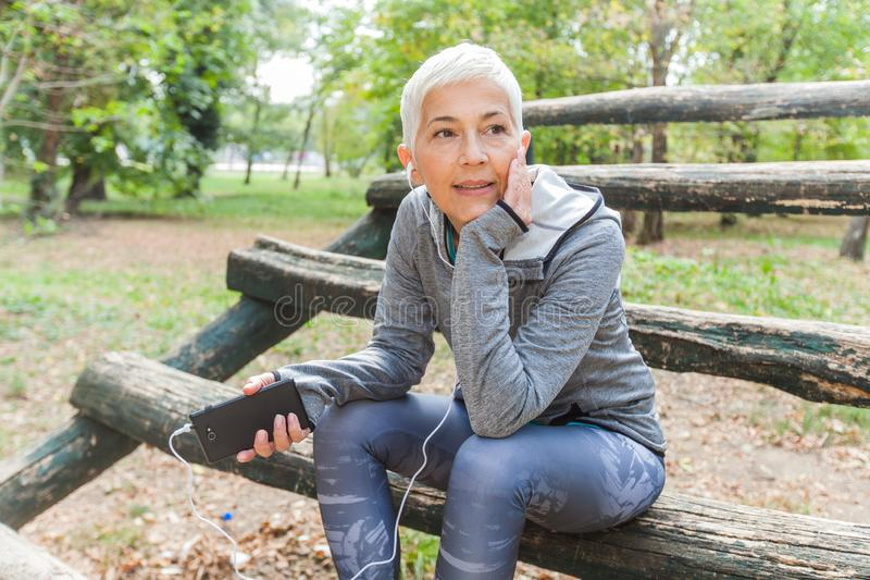 Senior Woman Relax Listening Music With Phone After Jogging In Forest. Healthy Lifestyle Workout Outdoor stock photo