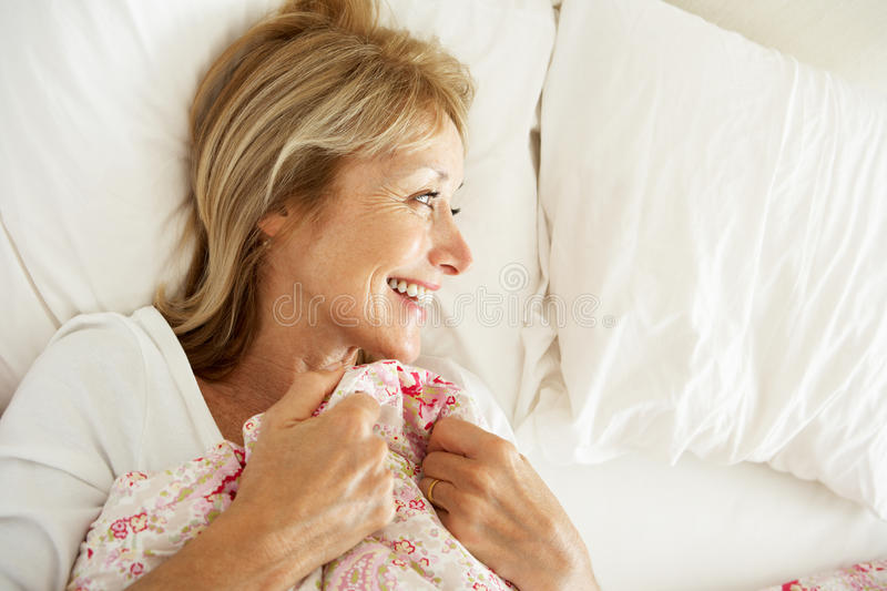 Senior Woman Relaxing In Bed