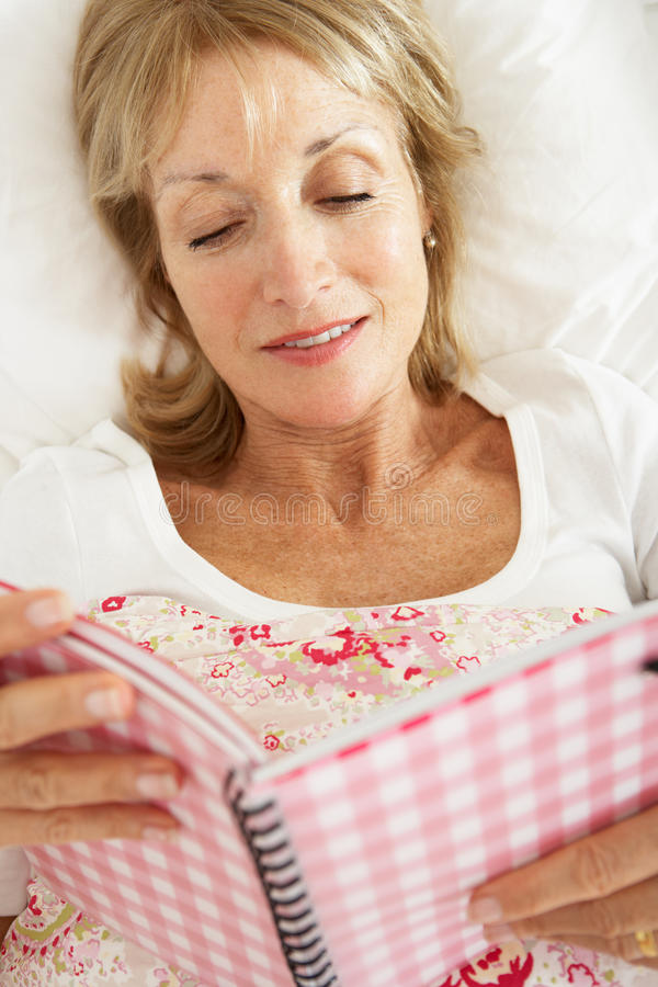 Download Senior Woman Relaxing In Bed Reading Diary Stock Photo - Image: 26616316