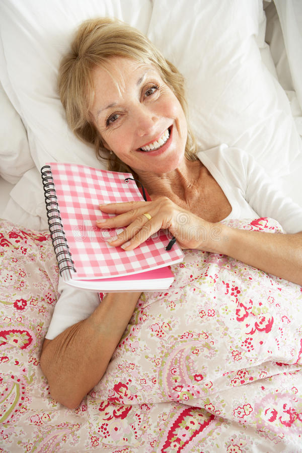 Download Senior Woman Relaxing In Bed Reading Diary Royalty Free Stock Images - Image: 26616319