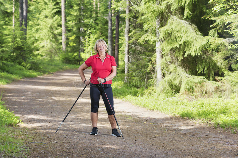 Senior woman relaxing and doing nordic walking royalty free stock photo