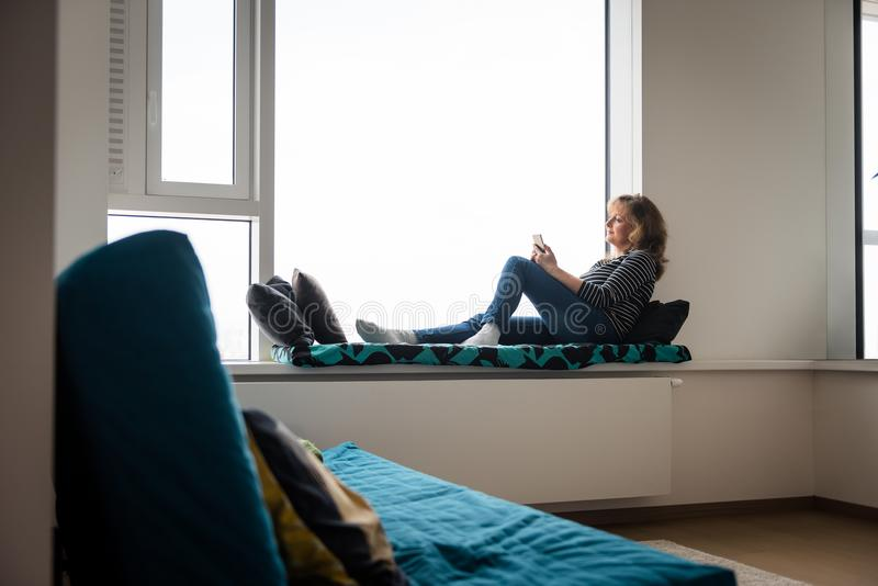 Mature woman sitting on window ledge bed stock photos