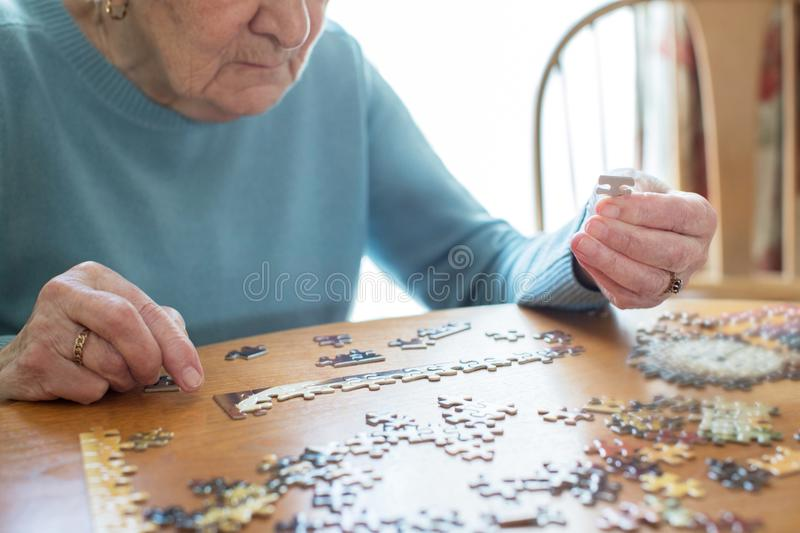 Close Up Of Senior Woman Relaxing With Jigsaw Puzzle At Home stock images