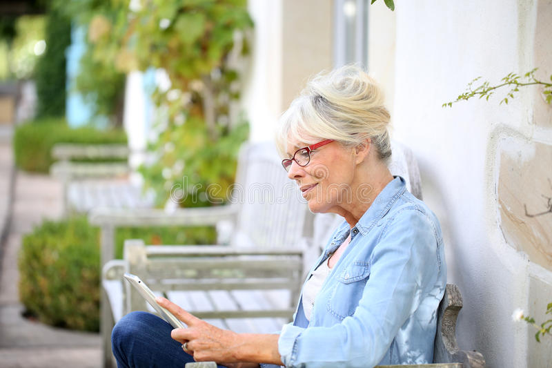 Senior woman relaxing outdoors with tablet royalty free stock photos