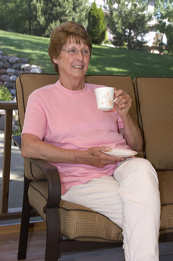 Senior Woman Relaxing on the patio royalty free stock photos