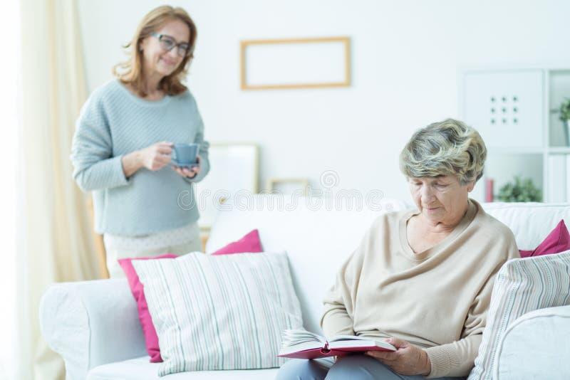 Senior woman relaxing on sofa. Photo of senior women relaxing on sofa reading book stock photography