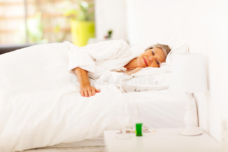 Senior woman resting. On bed at home stock photo