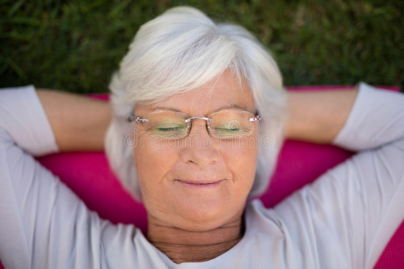 Senior woman resting with closed eyes on exercise mat royalty free stock photos