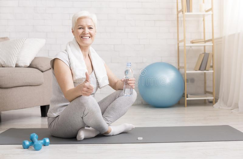 Senior woman resting on exercise mat after fitness workout royalty free stock images
