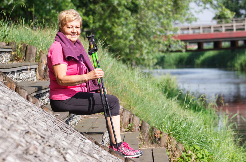 Senior woman resting after nordic walking on riverside, sporty lifestyles stock images