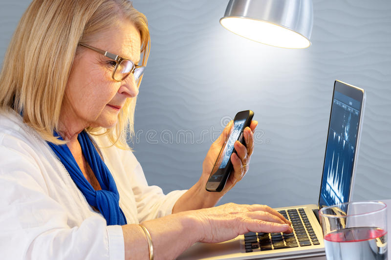 Senior woman reviewing cardio results on smart phone and laptop. stock photography