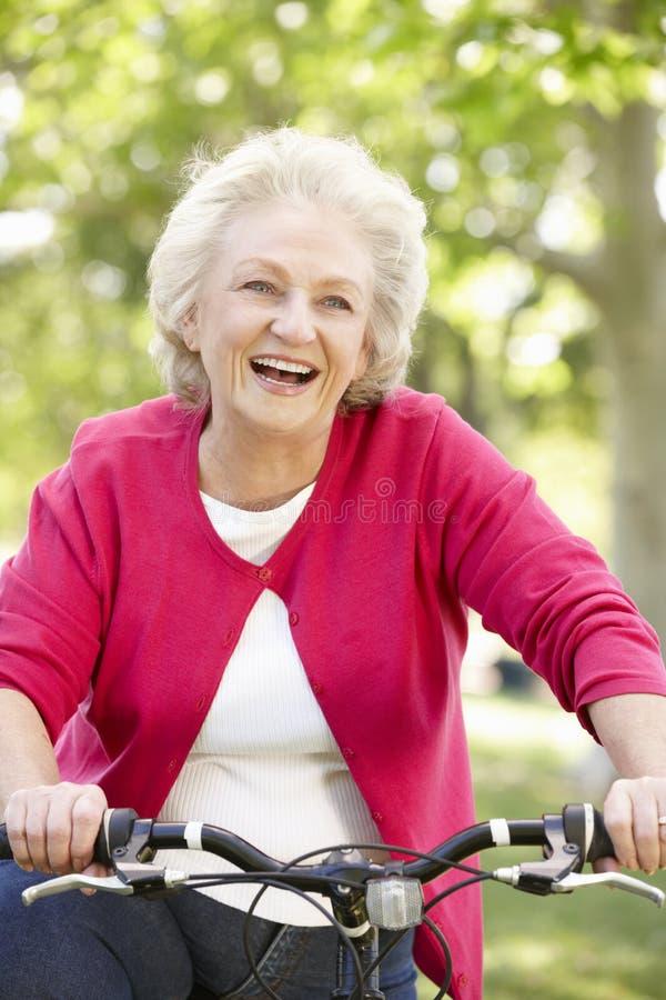 Senior woman riding bike stock photos