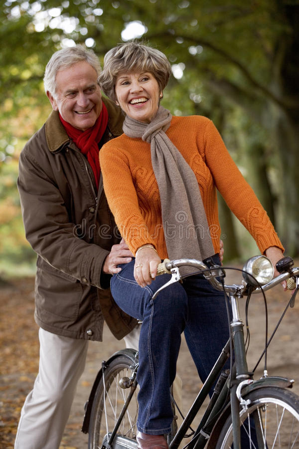 A senior woman riding a bike with her partner pushing her along stock image