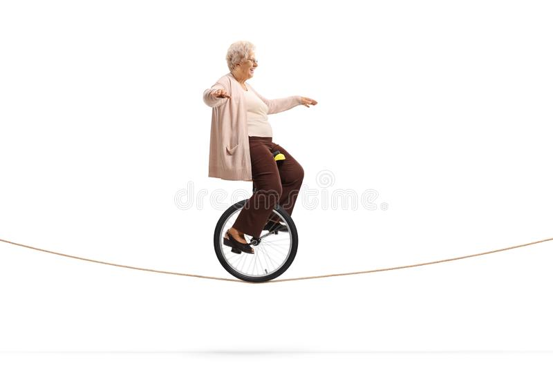 Senior woman riding a mono-cycle on a rope. Full length profile shot of a senior woman riding a mono-cycle on a rope isolated on white background royalty free stock image