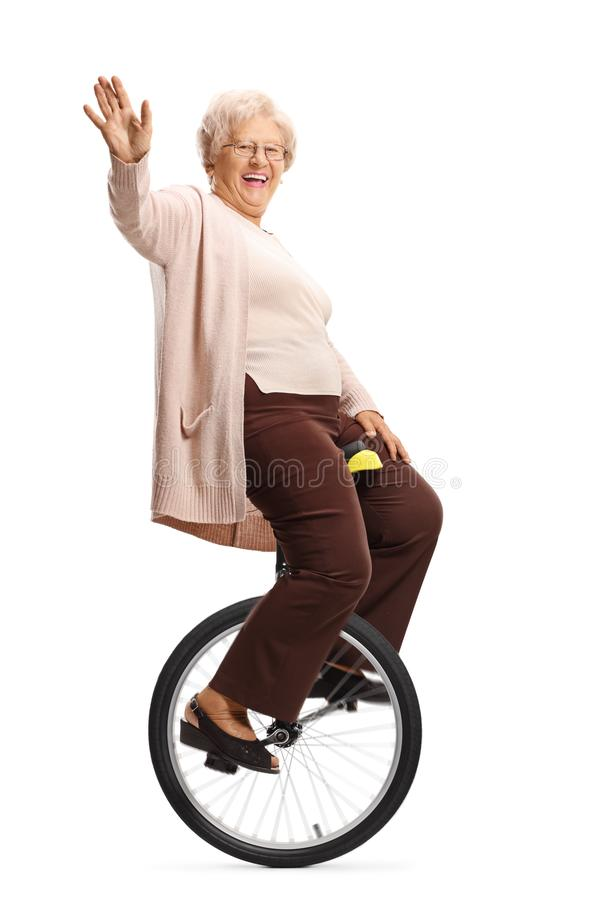 Senior woman riding a unicycle and waving at the camera. Full length shot of a senior woman riding a unicycle and waving at the camera isolated on white royalty free stock photography