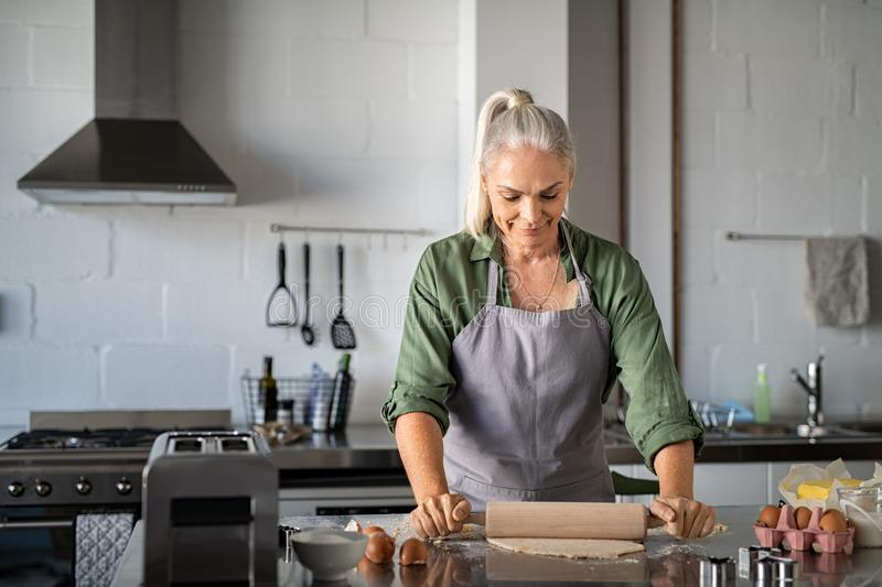 Senior woman rolling cookie dough at home stock photo