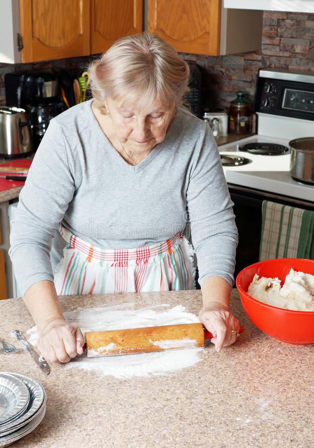 Senior woman rolling dough royalty free stock images