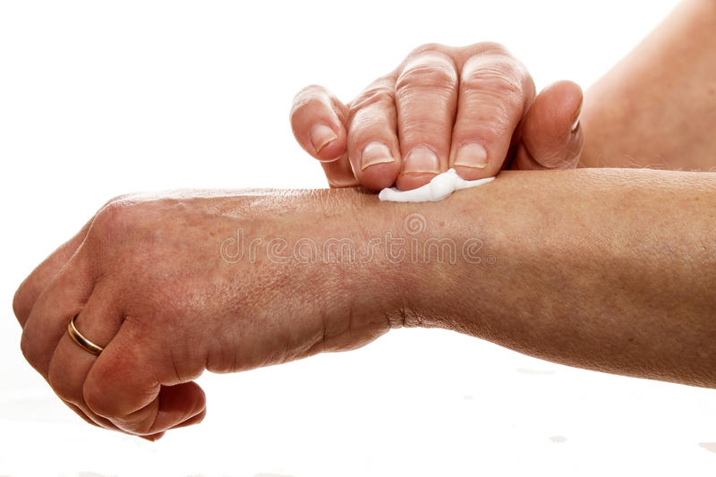Senior woman rubbing her wrist with a pain relieving cream. Senior female rubbing her wrist with a white pain relieving cream royalty free stock images