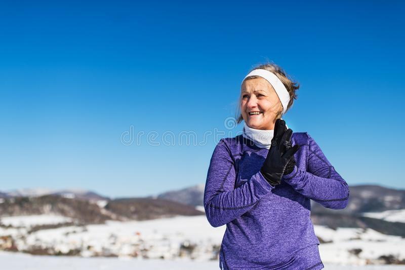 Senior woman runner resting in winter nature. Copy space. royalty free stock photography