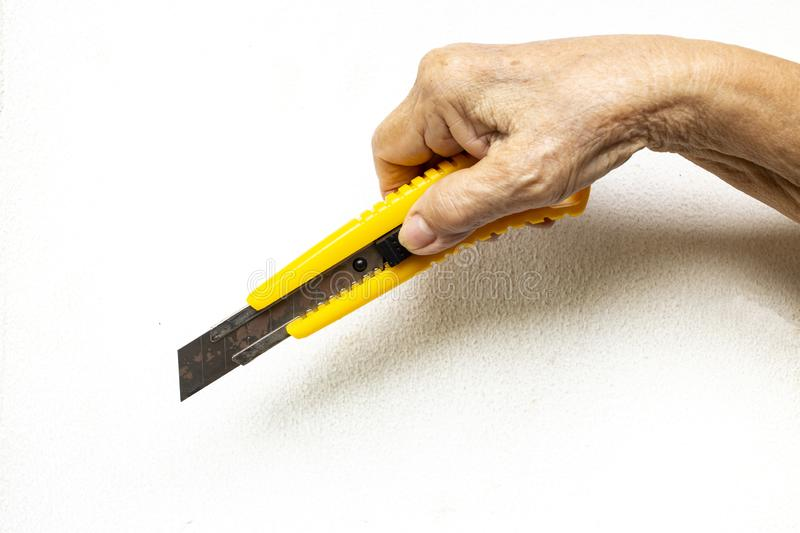 Senior woman`s hand holding a cutter knife on white background stock image