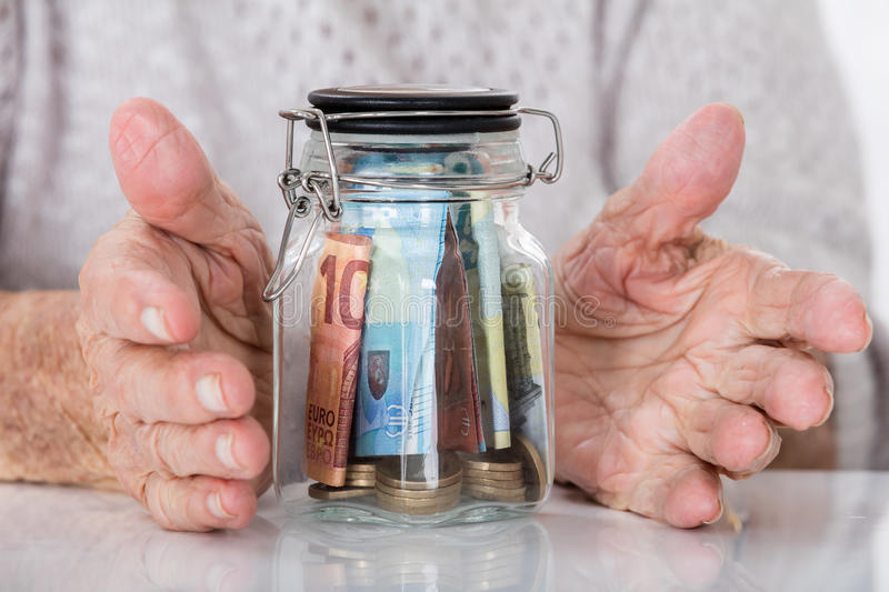 Senior Woman`s Hand Protecting Money Jar. Close-up Of Senior Woman`s Hand Protecting Glass Jar Of Money stock photos