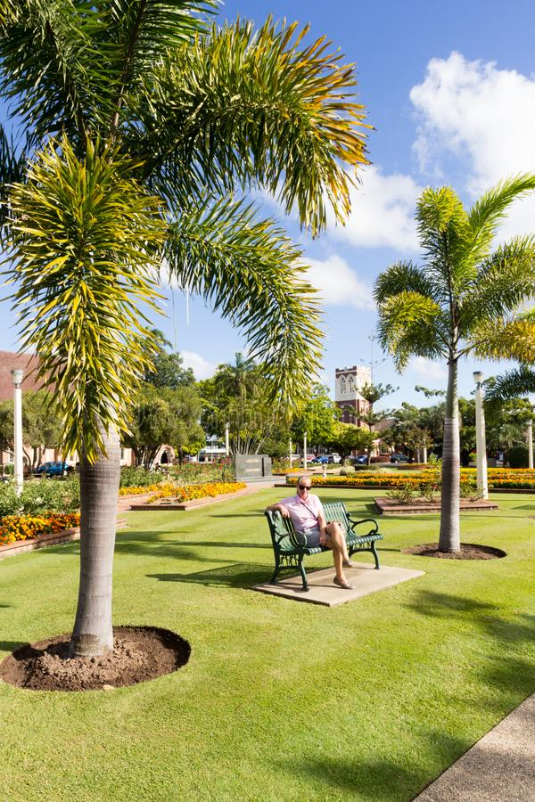 Senior woman sat in Buss park with the former Presyterian St Andrews church now Seventh Day Adventist church in the background,. Bundaberg, Australia - 19th May royalty free stock images