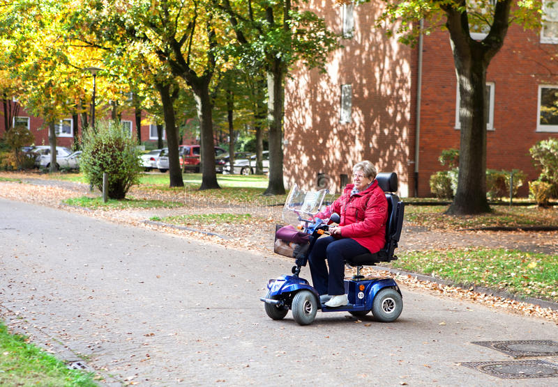 Senior woman with scooter 2 royalty free stock image