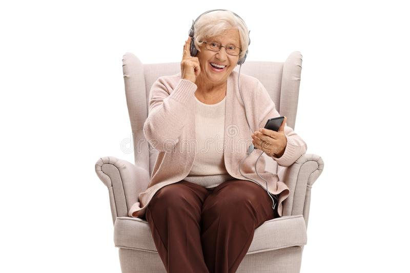 Senior woman seated in an armchair listening to music on a phone. And looking at the camera isolated on white background royalty free stock photos