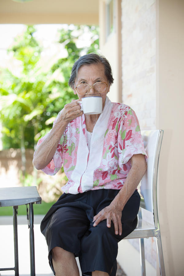 Senior woman seventy years old with good healthy life drinking a. White cup of hot water with relaxing emotion sitting on desk at home terrace and smiling royalty free stock images