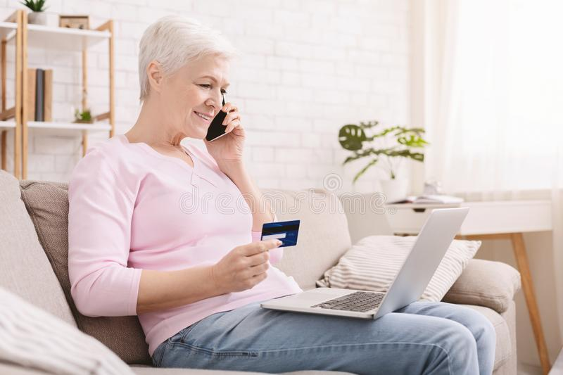 Senior woman shopping online and talking on phone. Senior woman shopping online through laptop with credit card and confirming her order by phone, empty space royalty free stock images