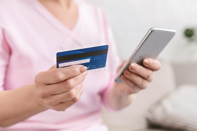 Senior woman shopping online with credit card and phone. Senior woman shopping online on smartphone, paying with credit card, closeup royalty free stock photography