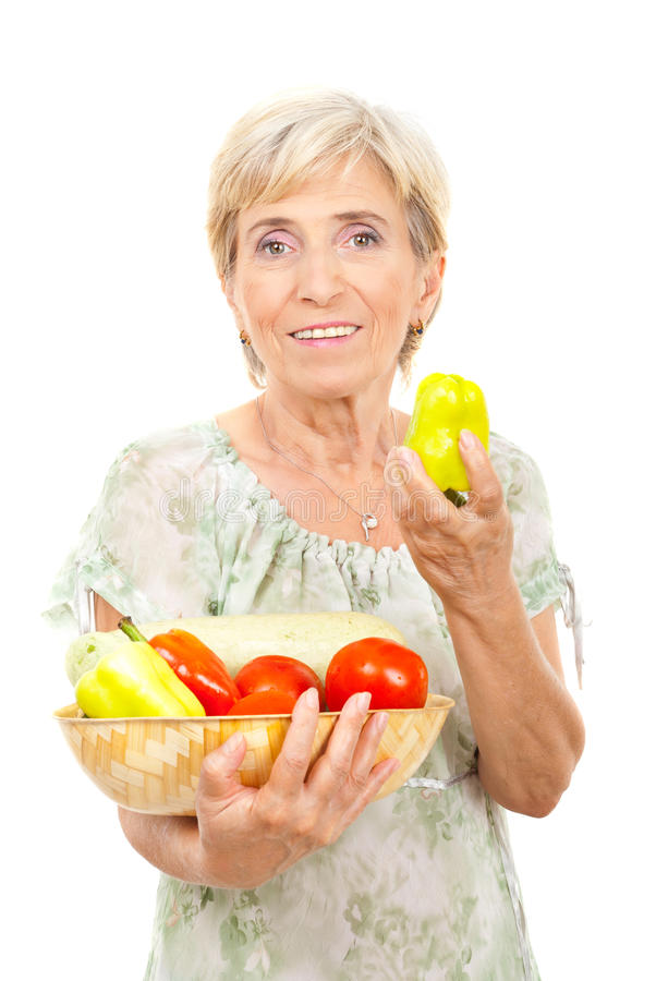 Senior woman showing a green pepper stock images