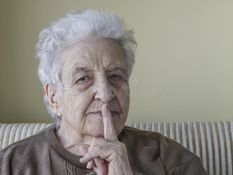 Senior woman showing hush silence sign with her finger stock photo
